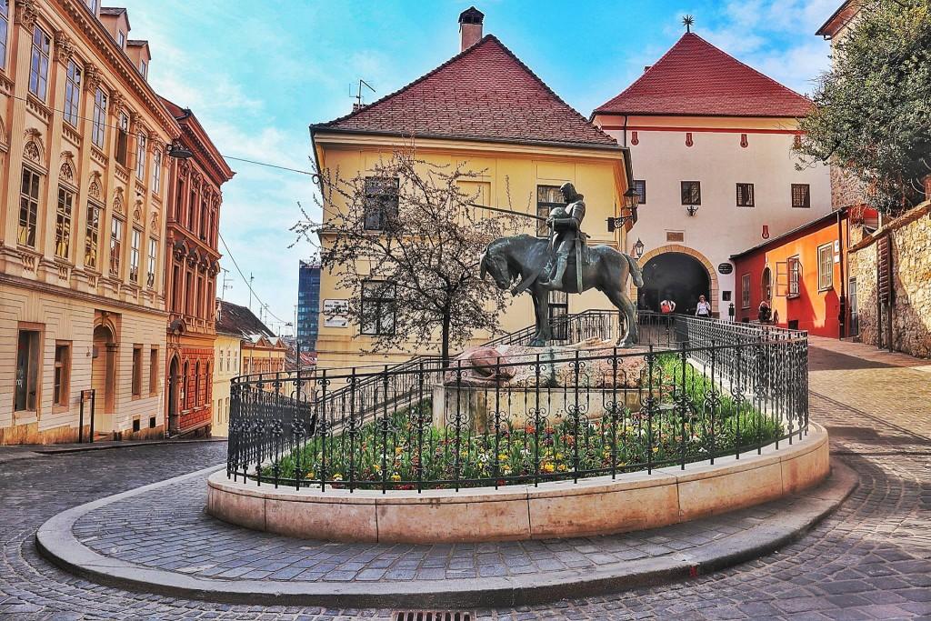 Sv. Juraj se moli i odaje počast protivniku. Kip je 1994. godine, na zahtjev Družbe Braća hrvatskog zmaja, postavljen ispred Kamenitih vrata.